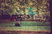 Őszi park és a lehullott levelek, emberek gyaloglás