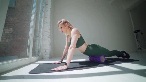 Junges schleimiges, flexibles sexy Mädchen, das Stretchübungen in Sportbekleidung macht. Fitte, sportliche Frau beim Yoga im Fitnessstudio. Katzenweibchen posieren im weißen Studio. Gesunder Lebensstil, nach oben gerichtete Hundehaltung.