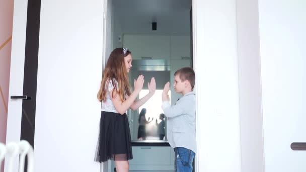 dva stylové veselé děti, bratr a sestra, malá holčička a chlapec tleskají rukama, hrají si ve svém pokoji, pohrávají si a smějí se. Smích a radost doma