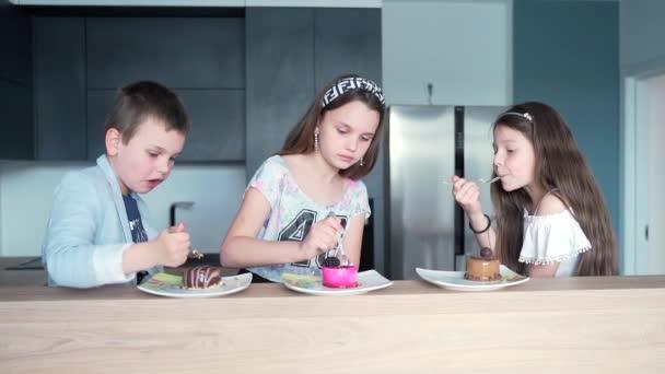 Šťastné děti sedící v kuchyni a ukazující palec nahoru, zatímco jedí lahodný dezert. Vtipné děti si vychutnávají jídlo v moderní stylové kuchyni. Mladé dívky a chlapec jíst lahodné jídlo a mají narozeninovou oslavu.