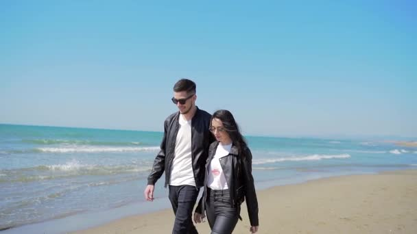 Fiatal elegáns pár sétál a tenger vagy az óceán partján a fehér homokban. Szerelmes barát és barátnő. Kézen fogva sétált a parton. Életstílus. Valentin nap. Szerelmi történet. boldog és vidám.