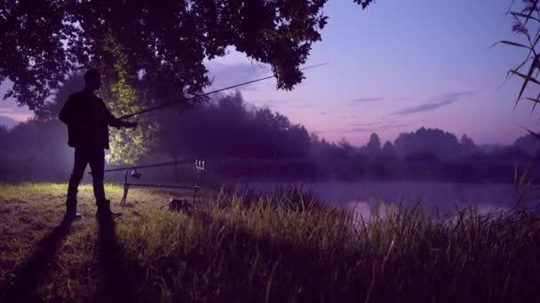 Silhouette egy férfi. fiatal férfi halász áll egy forgó horgászbottal a tó mellett. A fickó fogott egy halat, kezében egy tekercs. éjjel vagy reggel köd a víz felett, horgászfelszerelés. Kempingezés és kedvenc hobbi