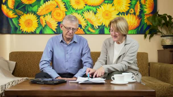 old couple man and woman counting checks and bills. Consider a bank statement loan or utilities. bank credit. Social benefits. insurance or medical. Retirees at home deal with documents a calculator