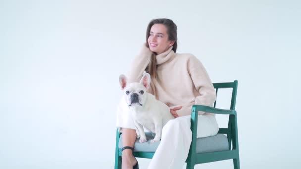 Vidám fiatal hölgy kötött pulóverben és fehér nadrágban ül a széken az aranyos francia bulldog-jával, mosolyog és a kamerába néz. Elszigetelve a fehér stúdió hátterétől. Nő és vicces kisállat kutya