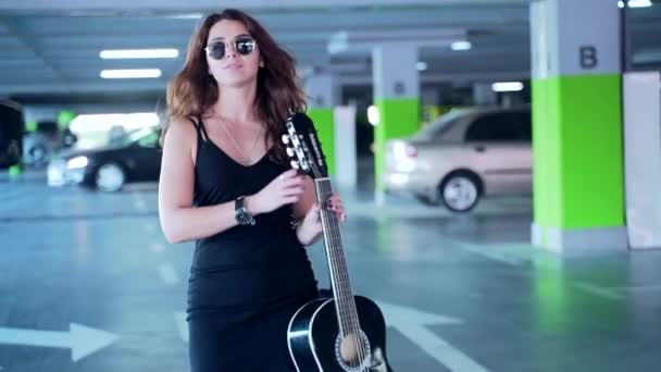 close up of fashionable young woman stylish girl with a guitar goes, walk and looking at camera in the parking lot in black stylish dress and sunglasses, fashion young adult woman. Urban background
