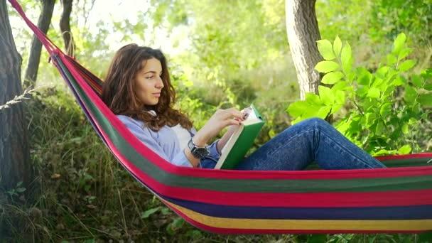 Okouzlující mladá dáma s tmavými vlasy ležící v barevné houpací síti v letním parku a čtení nové knihy. Koncepce volného času a vlastního vzdělávání.