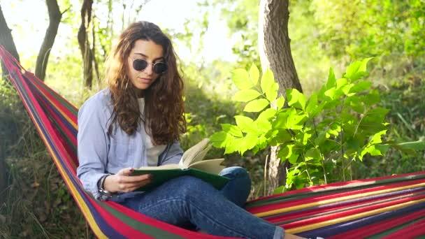 Okouzlující mladá dáma s tmavými vlasy ležící v barevné houpací síti v letním parku a čtení nové knihy. Koncept volného času a sebevzdělávání. Zavřít portrét