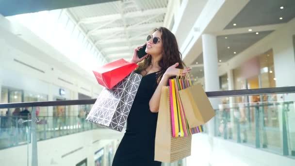 Egy fiatal, boldog, mosolygós boltos nő portréja, aki boldogan beszél a telefonon színes ajándékcsomagokkal a kezében. Göndör, vonzó hölgy áll a plázában, és otthon vásárol. Fekete péntek vagy Cyber hétfő