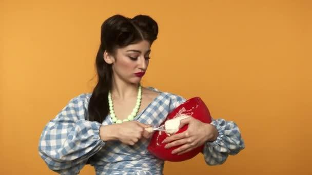 Irritierte Pin-up Hausfrau mit Teig Kochen auf gelbem Hintergrund