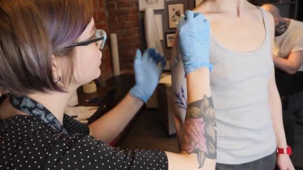 A tetováló művész dolgozik. A lány gazdaság egy tetováló gép és alkalmazott, a minta a bőr. Kék tintával a tetováló gép.