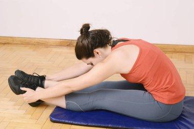 Portrait of sport woman streching legs. Indoors
