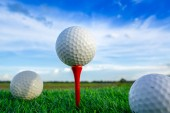 zavřít golfový míček na tee pegs připraven hrát v zeleném pozadí
