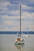 Fotografie Nichtbenutzte Segelboote liegen friedlich auf dem Wasser des Ammersees in Bayern