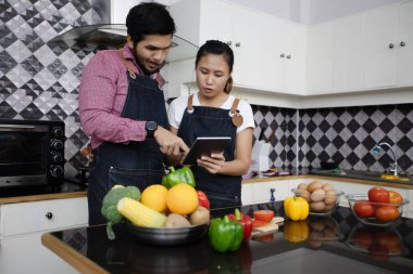 Happy and Smiling young couple cooking food in the kitchen at home