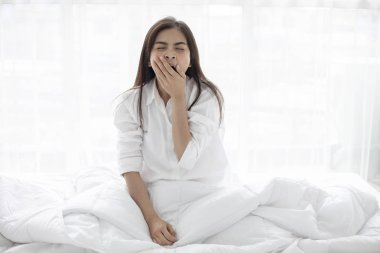 Asian woman Beautiful young smiling woman sitting on bed and stretching in the morning at bedroom after waking up in her bed fully rested and open the curtains in the morning to get fresh air.