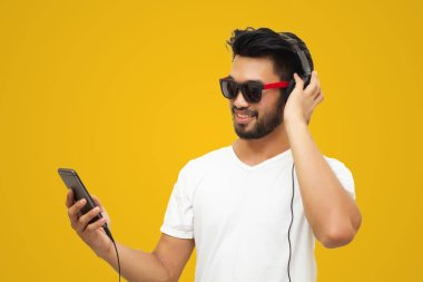 Asian handsome man using smartphone to listen music with headphones on yellow background