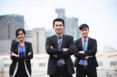 Skupina podnikatelských lidí s vedoucím obchodníka oslavuje úspěch a usmívající se