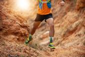 männlicher Athlet trägt Sportschuhe für Trail Running und Training auf Felsen bei Sonnenuntergang