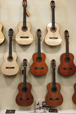 PORTO, PORTUGAL - APRIL 29, 2016: Rows of acoustic guitars on the wall in music store