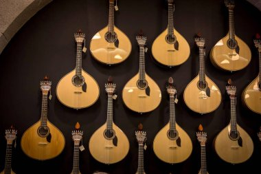 PORTO, PORTUGAL - APRIL 29, 2016: Rows of acoustic Portuguese guitars on the wall in music store