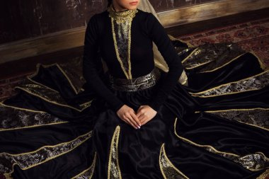 Young woman in armenian national dress posing in studio