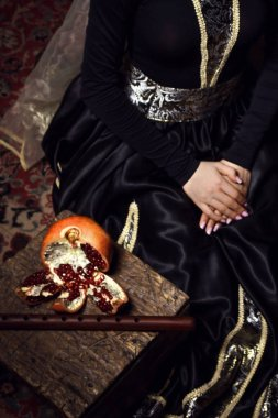 Young woman in armenian national dress sitting with pomegranate and duduk