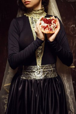 Young woman in armenian national dress with pomegranate in hands