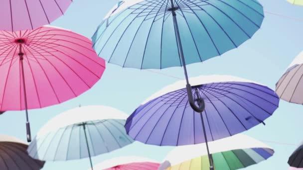 Fliegende Regenschirme. Bunte Regenschirme schweben in den Himmel. Regenschirme schwebten über ihren Köpfen. Ihr Wind weht