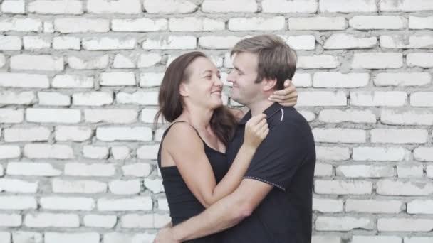 man and woman kissing and hugging at the camera