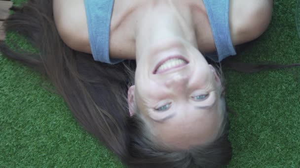 The girl lies on an artificial green lawn. She is laughing