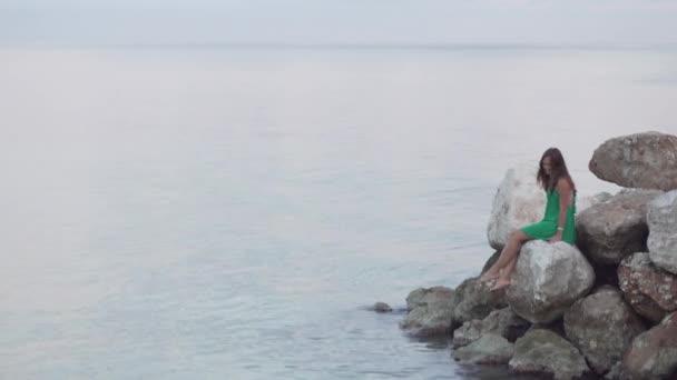 A woman sits on rocks near the sea.