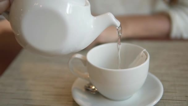 Female hand is holding a white kettle with boiling water over the cup