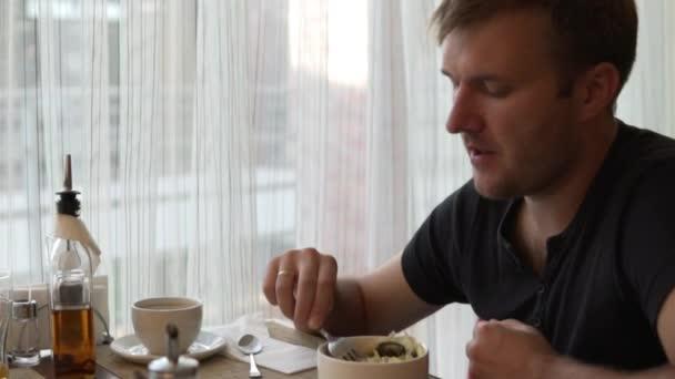 Muž u stolu v kavárně jí zeleninový salát