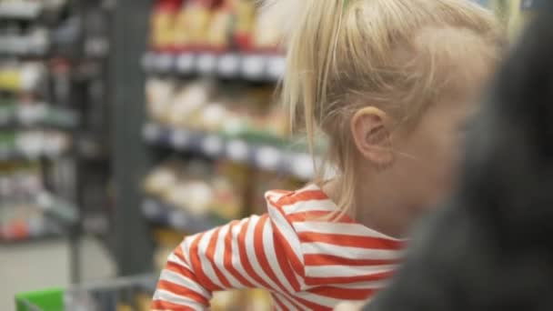Piccola ragazza divertente cavalca un carrello in un supermercato