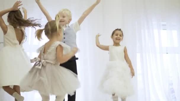 Krásné děti v elegantních šatech skok na jevišti
