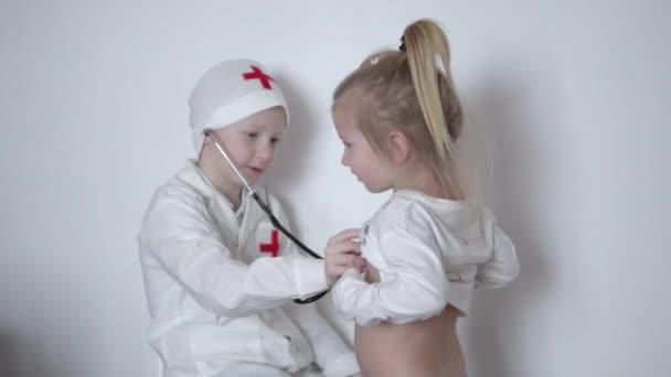 Děti hrají lékaře. Chlapec v bílém plášti poslechu holčička se stetoskopem