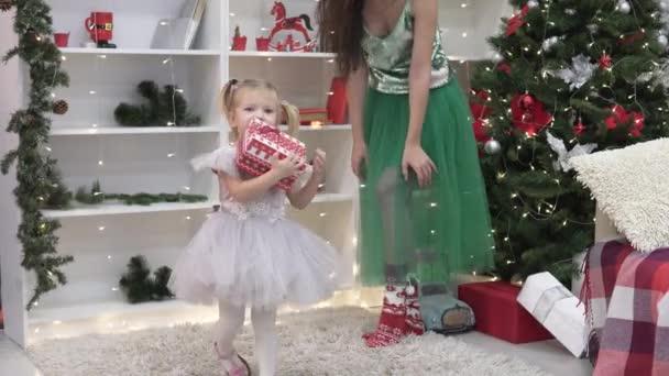 schöne elegante Frau macht einem kleinen Mädchen ein Neujahrsgeschenk