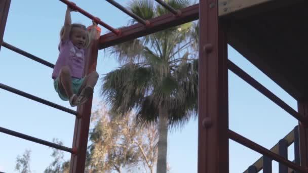 das Mädchen auf dem Spielplatz klettert auf den Griff und die waagerechte Stange.
