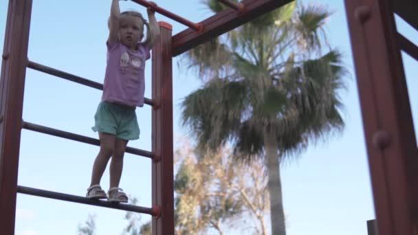 Tapferes kleines Mädchen hängt auf der Treppe auf dem Spielplatz