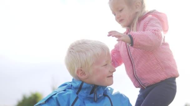 Egy kislány finoman megcsókolja a bátyja.