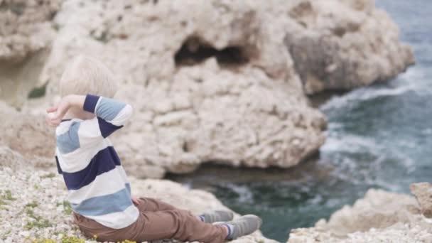 Egy csinos szőke fiú dob kövek a tengeren