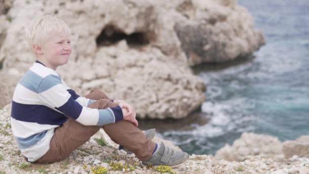 gyönyörű szőke fiú ül egy sziklán, és sziklák a tenger mellett