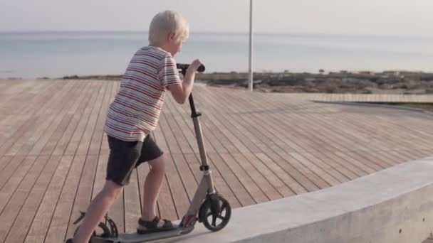 A child riding a scooter in the park by the sea.