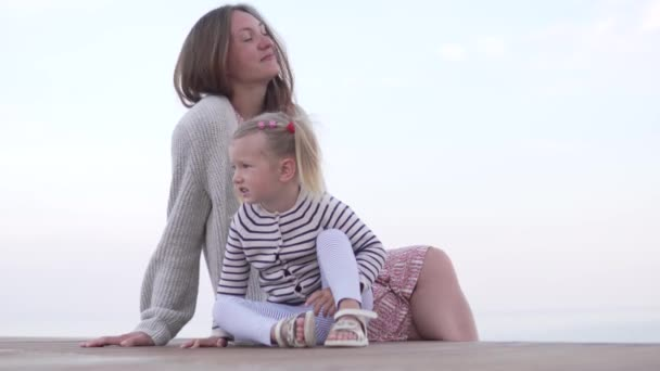 happy mother with her little daughter sitting on the beach at sunset