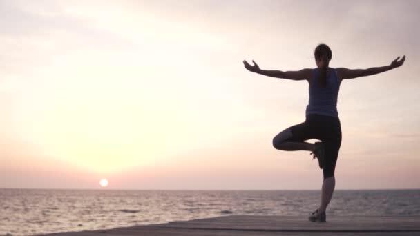 Egy nő jógázik naplementekor a tengernél. Fapózban áll.,