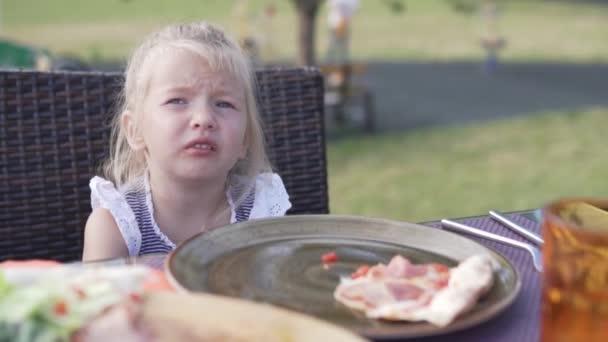 Roztomilá holčička, která jedla pizzu v kavárně na ulici