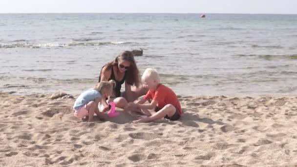 Máma s dětmi, co si hrají na pláži