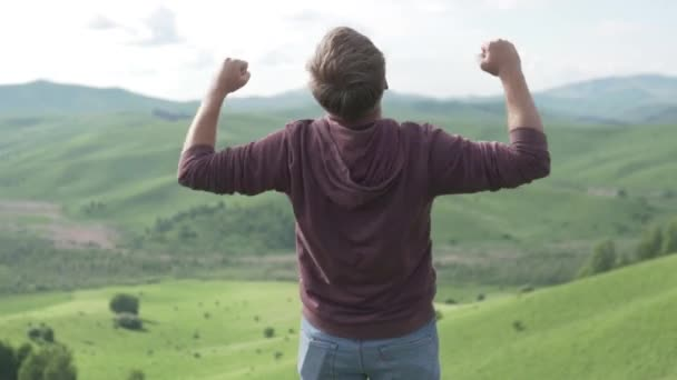 Male trekker raises arms enjoying mountain top view on summer