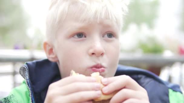 Hungry albino boy eating a hamburger on the street