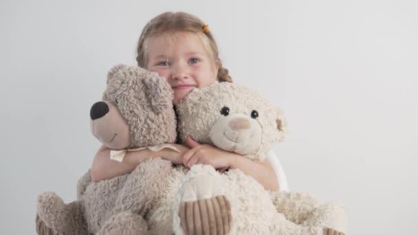 Közelkép egy gyönyörű kislányról két plüssmackóval